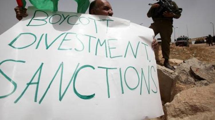 """Un Palestinien tient un panneau portant l'inscription """"Boycott, Divestment, Sanctions"""" (BDS) près de la colonie israélienne de Bat Ayin, à l'ouest d'Hébron (Cisjordanie), le 8 juin 2013"""