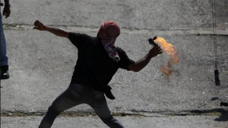 A Palestinian youth throws a Molotov cocktail towards Israeli soldiers close to the West Bank city of Ramallah  (Illustrative)
