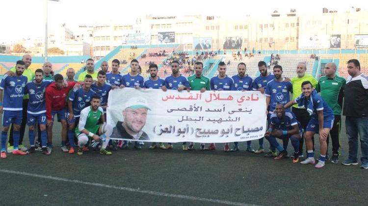 L'équipe de foot palestinienne Hilal al-Quds posant avec une banderole en hommage au terroriste palestiniens Mesbah Abu Sabih qui a tué deux israéliens dans une fusillade à Jérusalem le 9 October 2016.