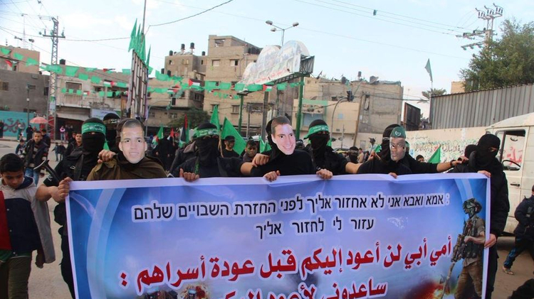 """Hamas militants march in Gaza with the faces of Israeli soldiers Oron Shaul, Hadar Goldin, and missing Ethiopian Avera Mengistu, holding banner reading: """"Mother and father, I will not return to you before Palestinian prisoners return home"""""""
