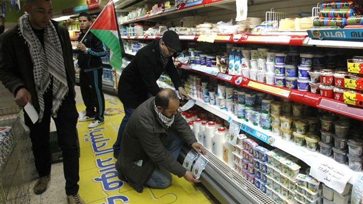 Palestinian activists stick leaflets calling for the boycott of Israeli products to a shelf selling Israeli dairy products in a supermarket in the town of Bethlehem i