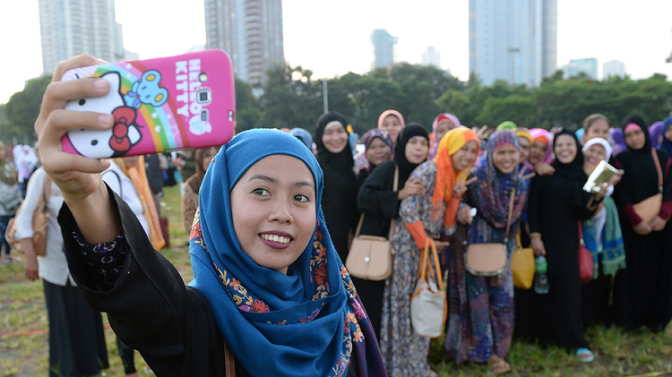 Muslim women pose for a selfie after attending prayers during Eid al-Adha celebrations at a park in Manila, the Philippines