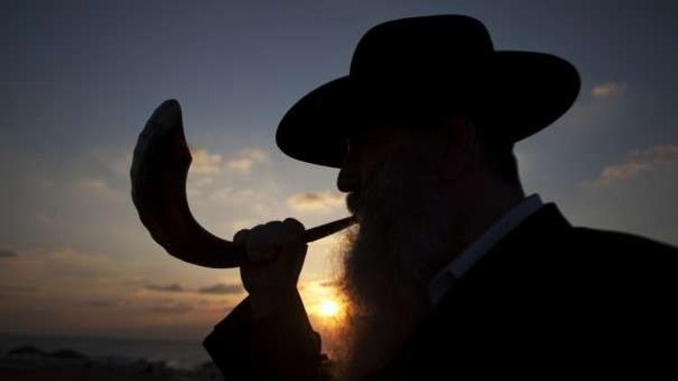 Jewish man blows ram's horn (shofar) during the High Holy Days
