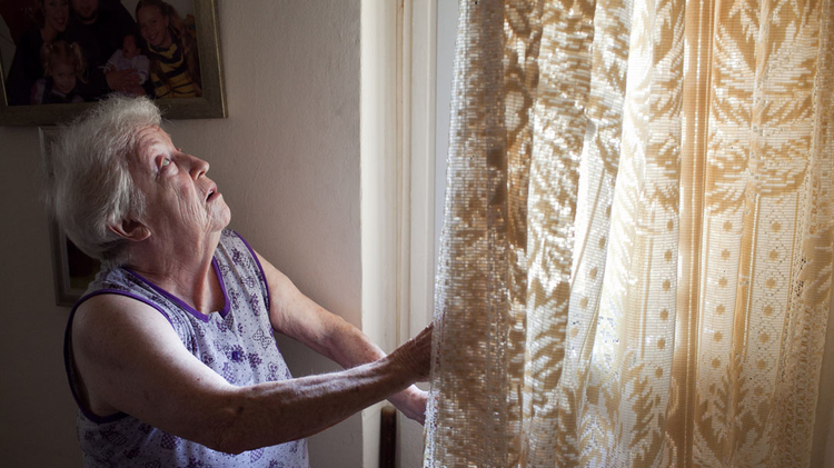 Holocaust survivor looks out window of her home in Ashkelon after rocket fell nearby