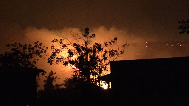Flames glow behind a the silhouette of a home in Nataf, the Jerusalem Hills, on November 25, 2016