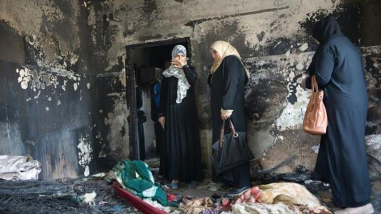 Des femmes palestiniennes constatent les dommages causés à une maison dans le village cisjordanien de Douma après l'incendie criminel perpétré par des extrémistes juif au mois de juillet 2015