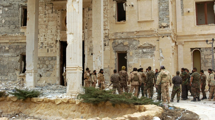 Syrian troops stand next to a mansion in the ancient city of Palmyra on March 24, 2016
