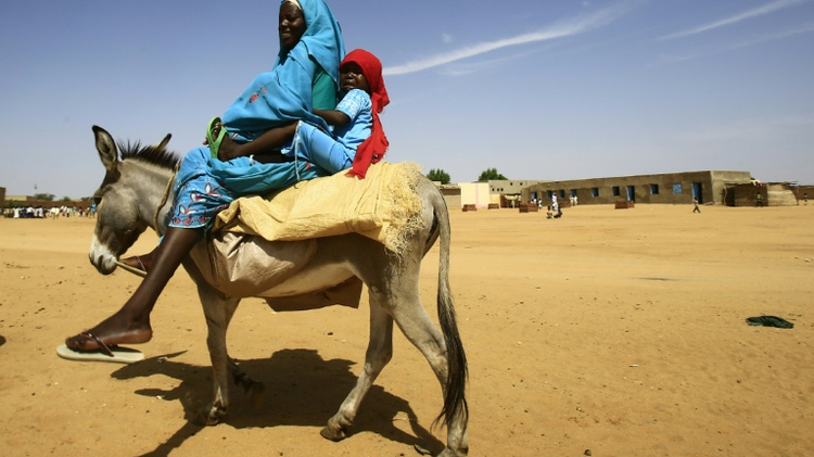 A woman and a boy ride a donkey in the Abu Shouk camp for Internally Displaced People in North Darfur on September 6, 2016