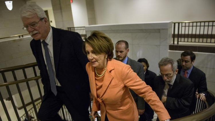 House Minority Leader Nancy Pelosi (R) leaves a meeting of House Democrats on Capitol Hill December 11, 2014 in Washington, DC