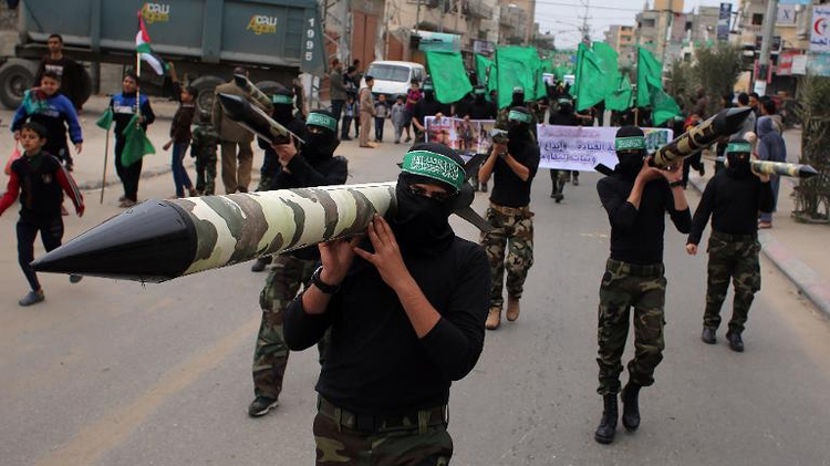 Palestinian militants from the Ezzedine al-Qassam brigade, the armed wing of Hamas, carry mock-rockets at a rally at the Nuseirat refugee camp in the Central Gaza Strip on December 12, 2014