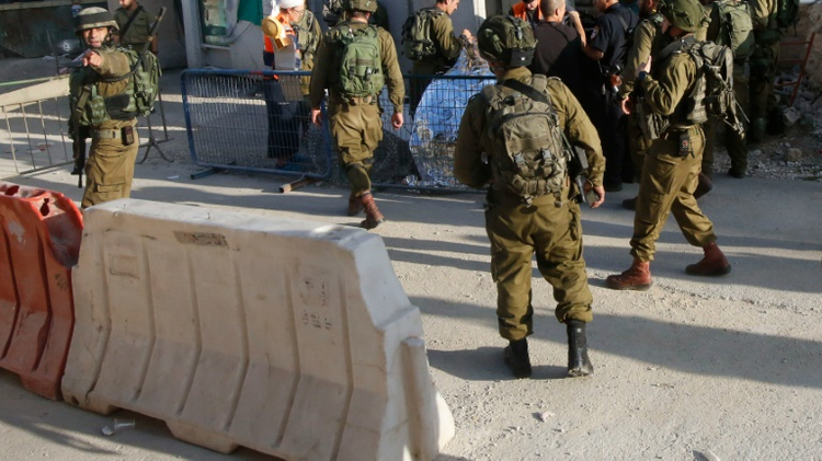 Israeli soldiers cover the body of a Palestinian shot dead after stabbing a soldier in Hebron