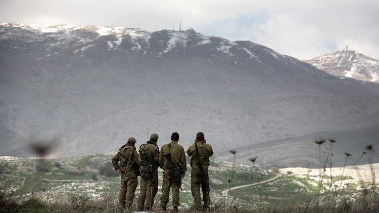 Israeli soldiers deployed on the border with Syria observe Syrian territory from Israeli side of the border near the Druze village of Majdal Shams, on March 19, 2014