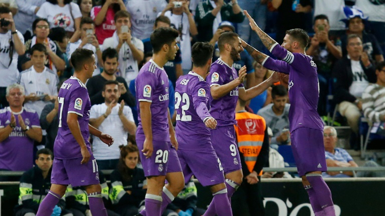 Real Madrid's French forward Karim Benzema celebrates with teammates after scoring during the Spanish league football match RCD Espanyol vs Real Madrid CF at the Cornella-El Prat stadium on September 18, 2016
