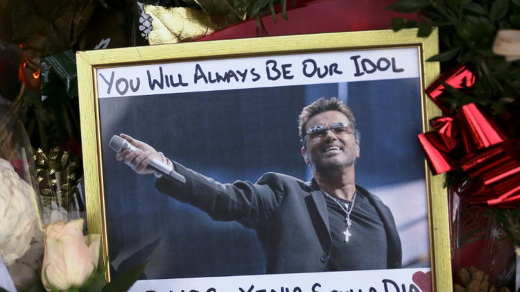 A photograph of British singer George Michael is seen among floral tributes and candles outside Michael's north London home on December 26, 2016