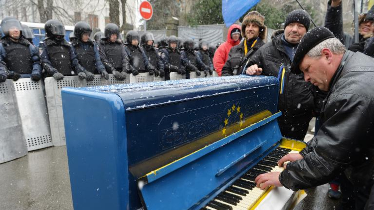 A man plays on a piano decorated as the EU flag in front of riot police as protesters picket Viktor Yanukovych's presidential office in Kiev on December 7, 2013