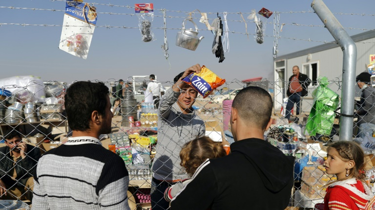 Internally displaced Iraqis, who fled the ongoing figthing between Islamic State (IS) group jihadists and government forces around Mosul, buy items from local vendors from behind the fence on November 28, 2016 at the al-Khazer refugee camp