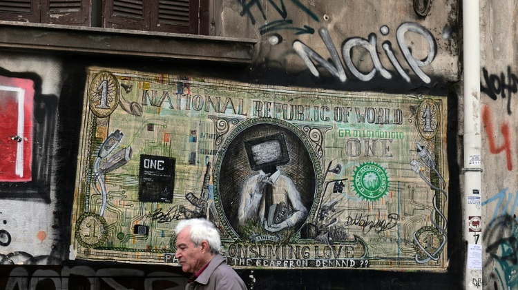 A man walks past a graffiti in the center of Athens on February 4, 2015
