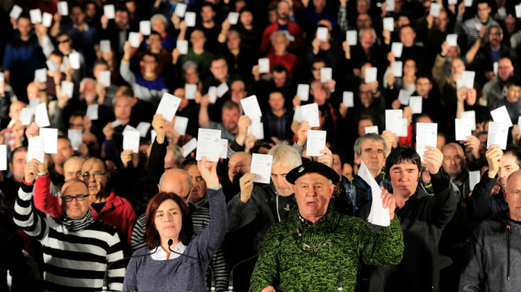 Ex-prisoners from armed Basque separatist group ETA hold up ballot papers in a demonstration in the Spanish Basque city of San Sebastian on December 12, 2015 to demand votes in the upcoming Spanish general election