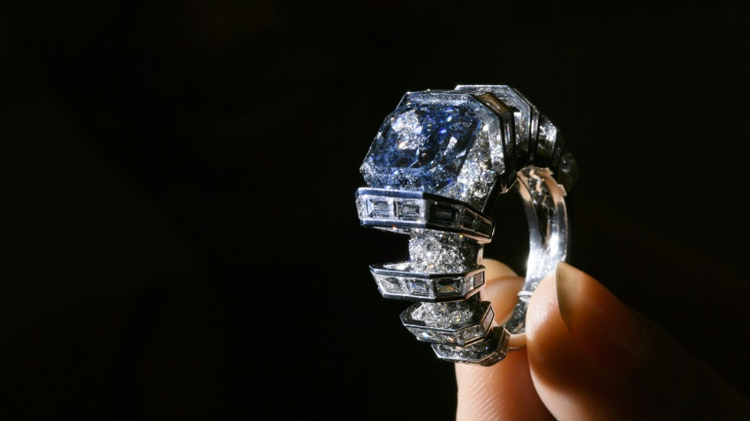 """A model presents the """"The Sky Blue Diamond,"""" a fancy, vivid blue diamond ring created by Cartier, during a press preview by Sotheby's Auction House on November 9, 2016 in Geneva"""