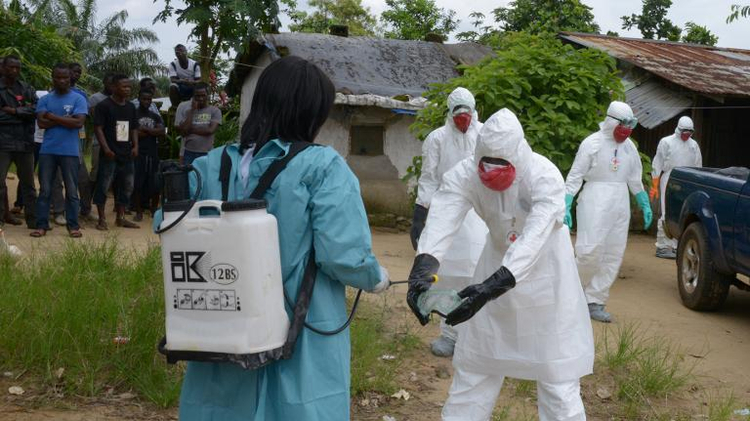 Medical workers from the Liberian Red Cross disinfect themselves in the small city of Banjol, where three people infected with the Ebola virus died, on September 4, 2014