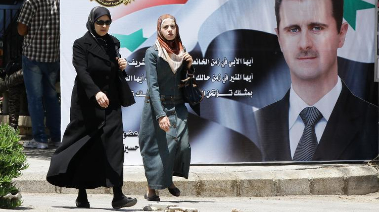 Two women walk past a huge billboard bearing a portrait of Syrian President Bashar al-Assad in the capital Damascus on May 27, 2014