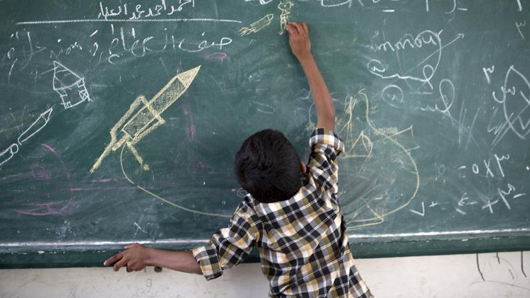 A Palestinian boy draws on a chalk board at a UN school after evacuating his home near the border in Gaza City on July 13, 2014