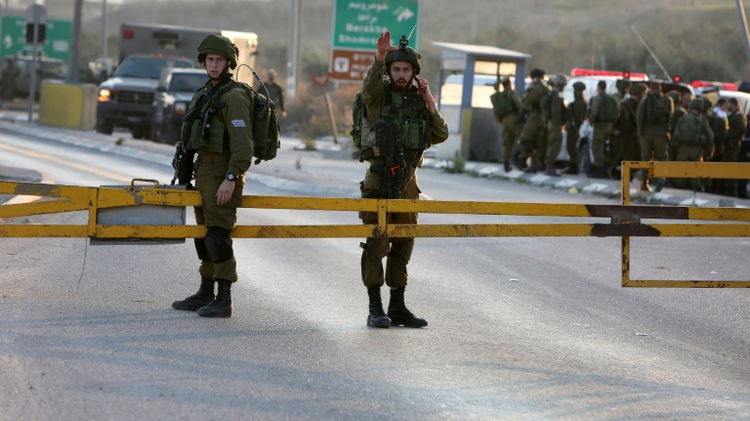 Israeli security forces stand guard at the site of a car ramming attack at the Huwara checkpoint near the West Bank city of Nablus, on December 26, 2015
