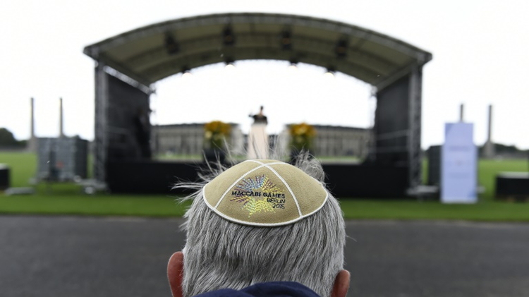 "A man wears a Kippa at the so-called ""Maifeld"" near the Olympic Stadium of Berlin, during a Memorial ceremony for the victims of the Holocaust before the official opening ceremony of the 14th European Maccabi Games in Berlin, on July 28, 2015"