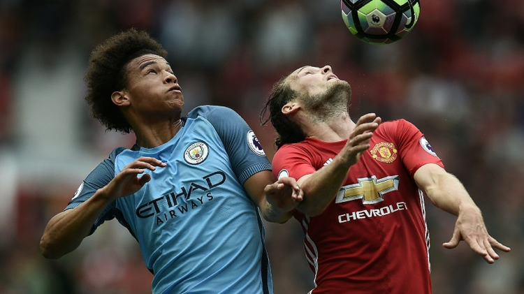 Manchester City's Leroy Sane (L) fights for the ball with Manchester United's Daley Blind during their English Premier League match, at Old Trafford, on September 10, 2016