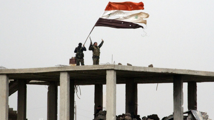 Syrian government forces wave the national flag in Deir al-Adas in the Daraa province on February 11, 2015 after President Bashar al-Assad's army, backed by Hezbollah and Iranian officers, pushed rebels out of the area  (Illustrative)