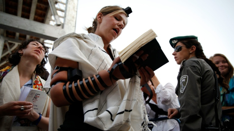 An Israeli police woman stands guard near members of the liberal Jewish religious group Women of the Wall wearing traditional Jewish prayer apparel for men, as they pray at the Western Wall in Jerusalem