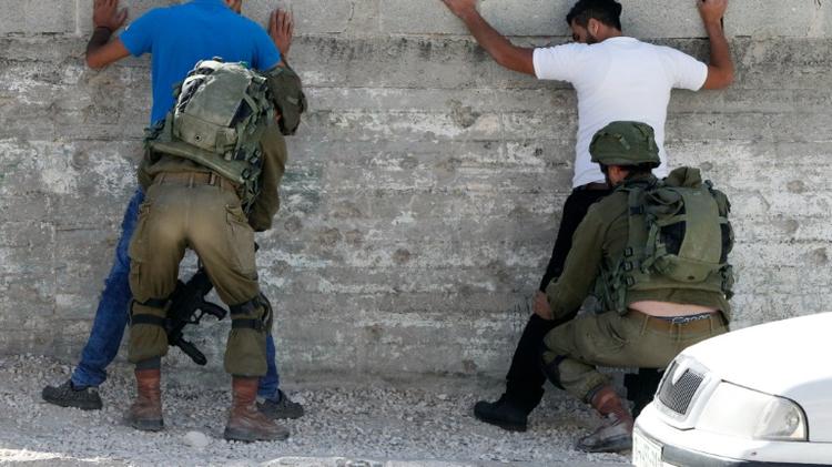 Israeli soldiers frisking Palestinians in Hebron