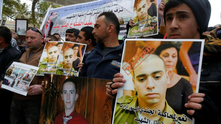 Protesters hold pictures of Israeli soldier Elor Azaria and Palestinian Abdul Fatah al-Sharif shot by Azaria