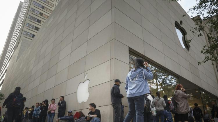Customers wait outside an Apple store