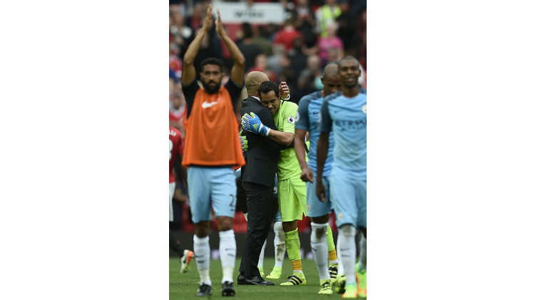 Manchester City's manager Pep Guardiola embraces goalkeeper Claudio Bravo as they celebrate after defeating Manchester United in their English Premier League match, at Old Trafford, on September 10, 2016