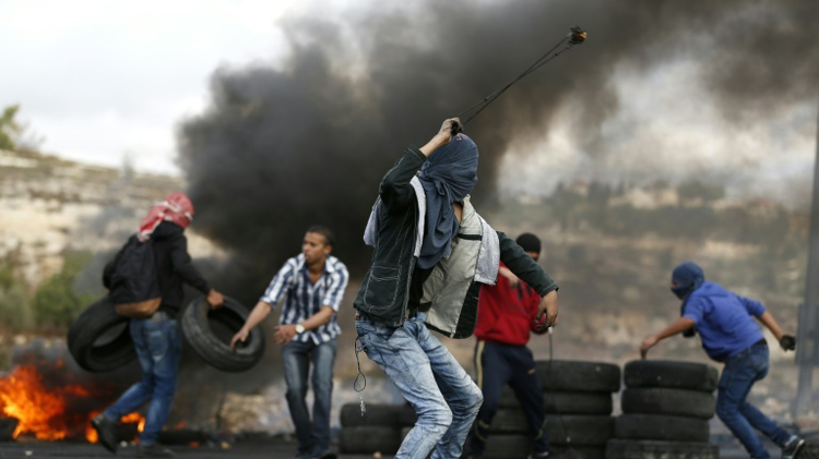 Palestinian protesters throw stones towards Israeli security forces during clashes at the northern entrance of the West Bank town of Al-Bireh, on the northern outskirts of Ramallah, in the West Bank, on October 27, 2015