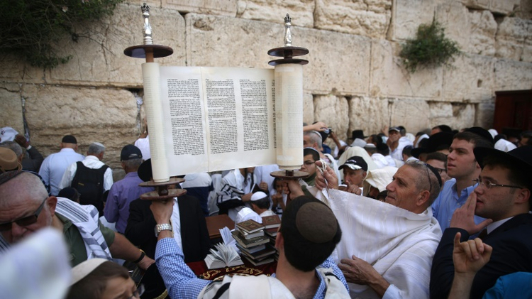 Jewish men, draped in prayer shawls, lift the Torah as they take part in the Cohanim prayer (priest's blessing) at the Western Wall in the Old City of Jerusalem on April 25, 2016