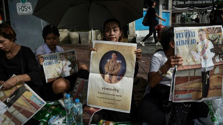 People hold newspaper images of Thailand's new King Maha Vajiralongkorn outside the Grand Palace in Bangkok