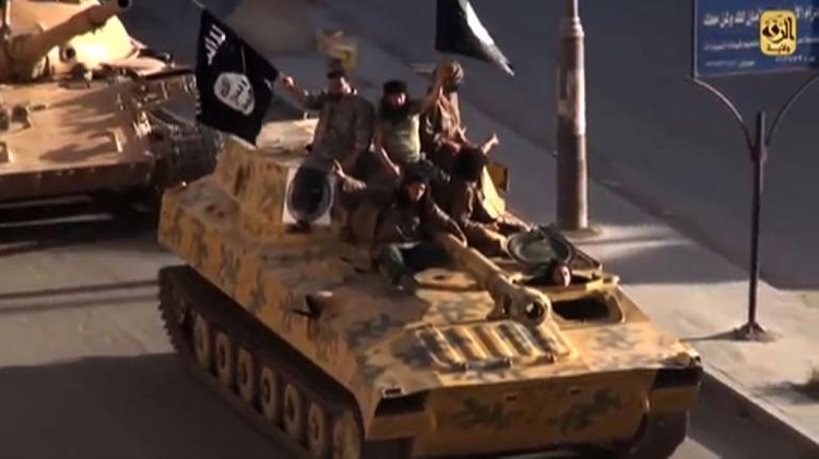 A screen grab taken from a video released on July 1, 2014, allegedly shows members of the IS (Islamic State) parading on top of a tank on a street in the northern rebel-held Syrian city of Raqa