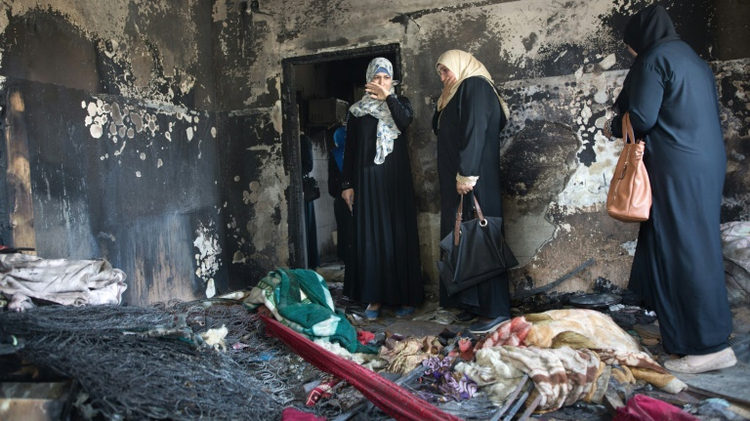 Palestinian women look at the damage to a home in the West Bank village of Duma on August 4, 2015, after it was set on fire by suspected Jewish extremists killing 18-month-old Ali Saad Dawabsha