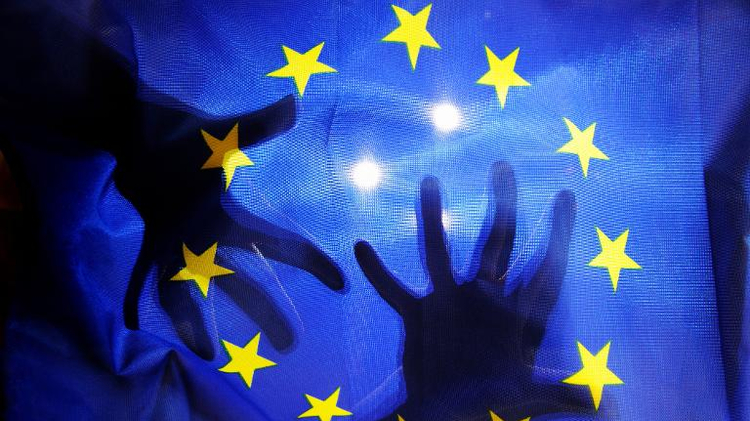 Picture taken on October 13, 2012 in Lille shows an illustration showing the silhouette of hands behind a European Union flag