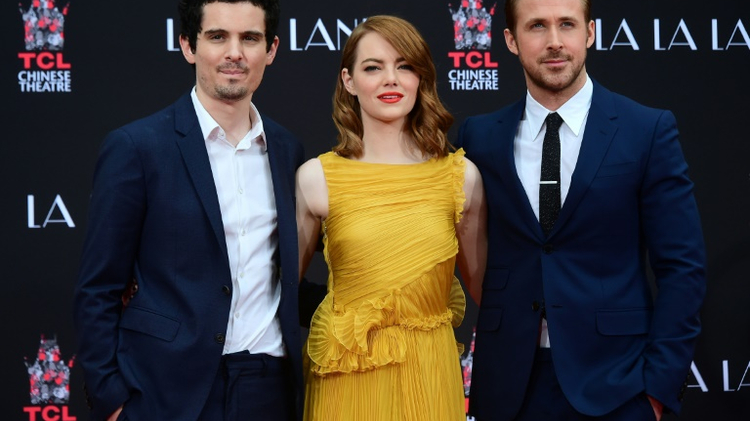 Actors Emma Stone (C) and Ryan Gosling (R) pose alongside director Damien Chazelle in Hollywood on December 7, 2016