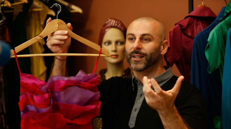 Palestinian American fashion designer Rami Kashou shows one of his designs, during a fitting session, at a pop-up  shop in the West Bank city of Ramallah