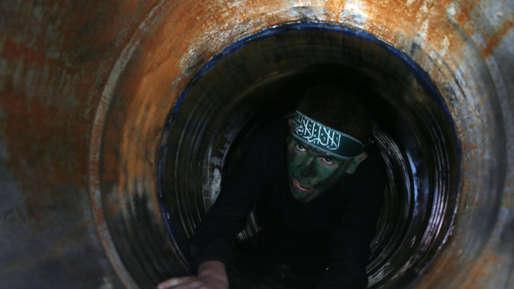 A Palestinian youth crawls in a tunnel during a graduation ceremony for a training camp run by the Hamas movement on January 29, 2015 in Khan Yunis, in the southern Gaza Strip