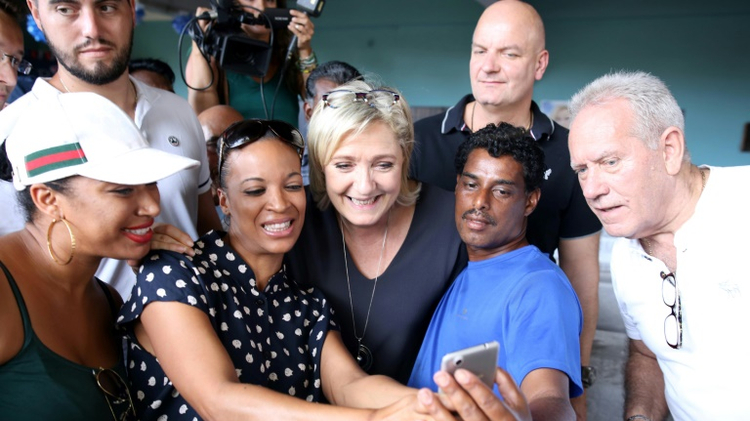 French Front National far-right party's President, European MP and presidential candidate for the 2017 election Marine Le Pen (C) poses for a picture with supporters on November 27, 2016