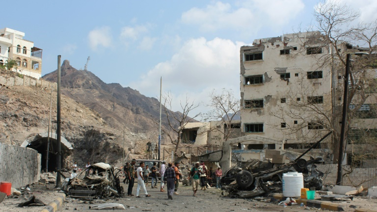 Armed Yemeni men look at the wreckage of a vehicle in the aftermath of a suicide car bombing on January 18, 2016 on the residence of Aden's police chief, General Shalal Shaea