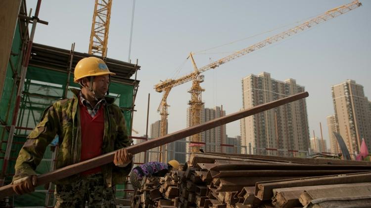 Un ouvrier pose des barres d'acier dans un chantier à Pékin, le 15 avril 2016