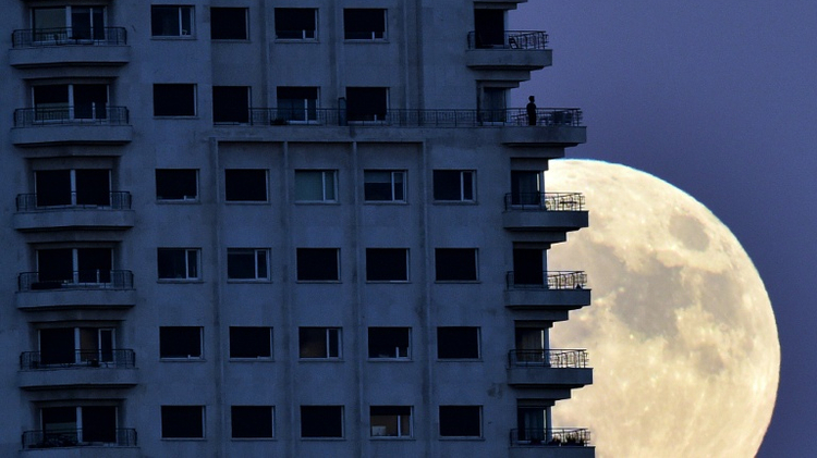 """A man stands on a balcony of a Madrid as the moon rises in background on the eve of a """"supermoon"""""""