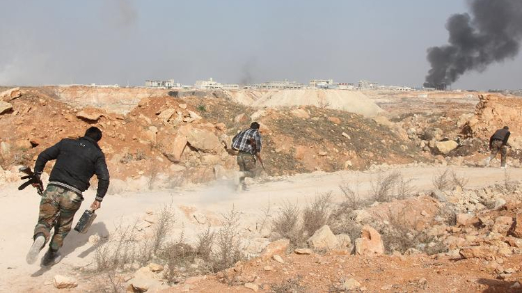 Rebel fighters run for cover during reported battles against pro-government forces in February 2014, in the Sheikh Najjar district on the outskirts of the northern Syrian city of Aleppo