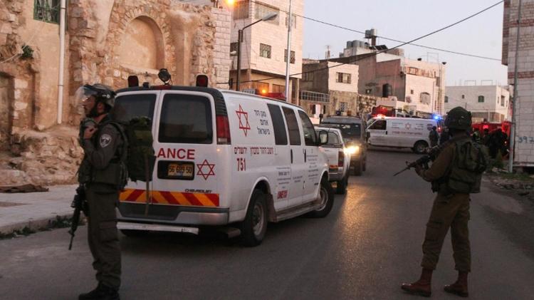 Des ambulances et des membres des forces de sécurité israéliennes, le 14 février 2016 à Hébron en Cisjordanie